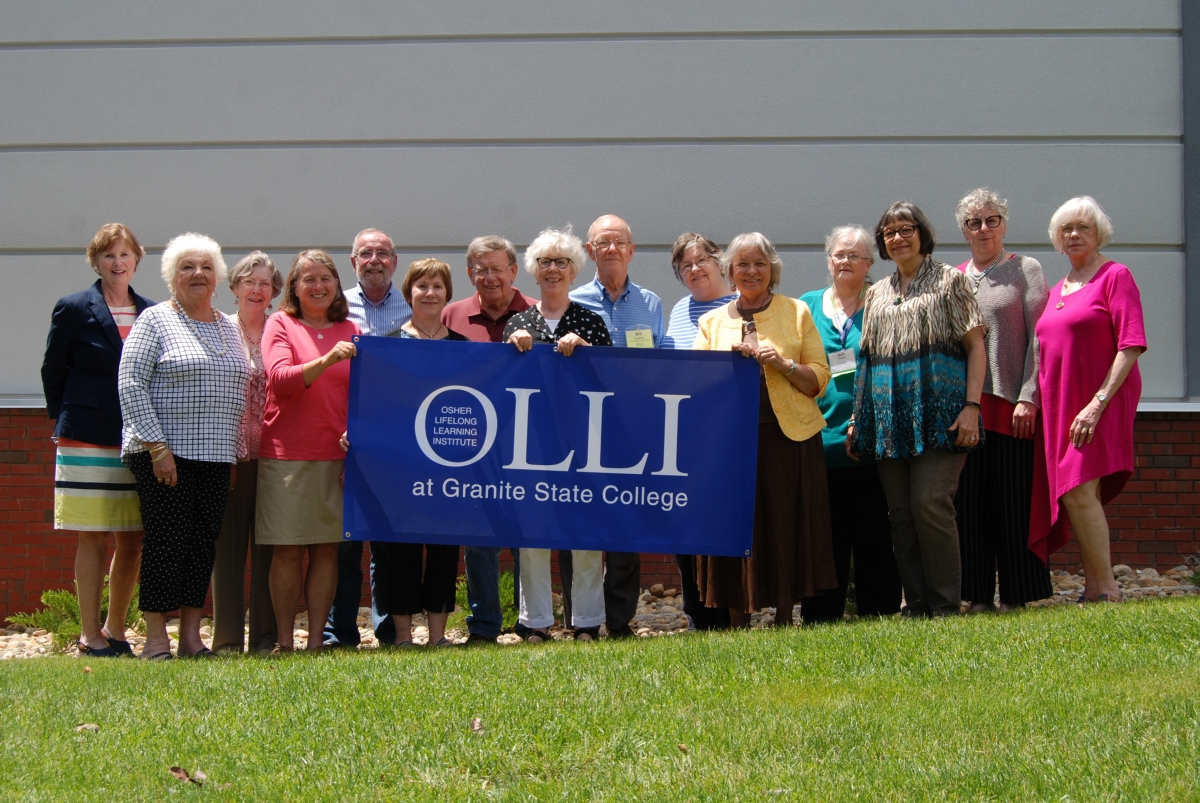 A group of OLLI at Granite State College leadership holding an OLLI banner.
