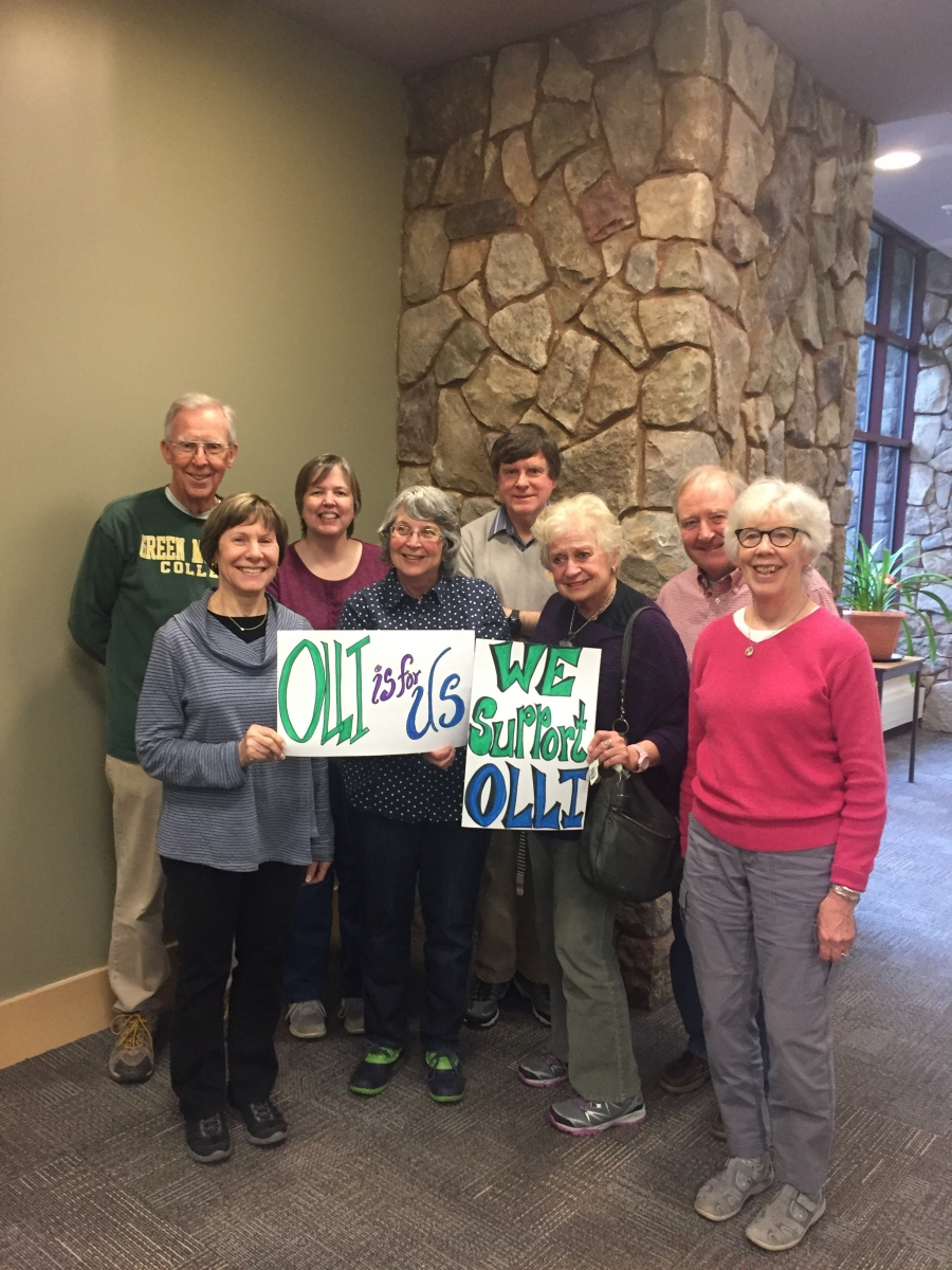 A group of Conway Members holding signs supporting OLLI